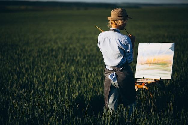 Pittura dell'artista della donna con le pitture ad olio in un campo
