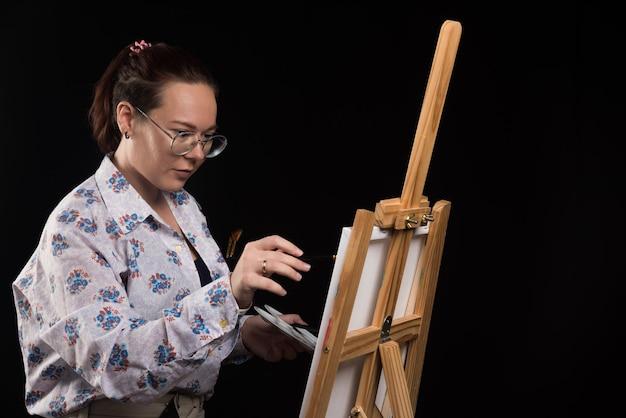 Художница рисует картину на холсте карандашом на черном