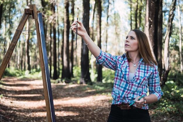 女性アーティストが屋外で絵を描きます。絵画における芸術家の測定。