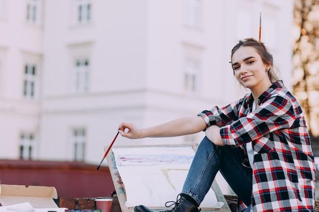 Художник женщины красит изображение пока сидящ на кирпичной стене на предпосылке старой архитектуры.
