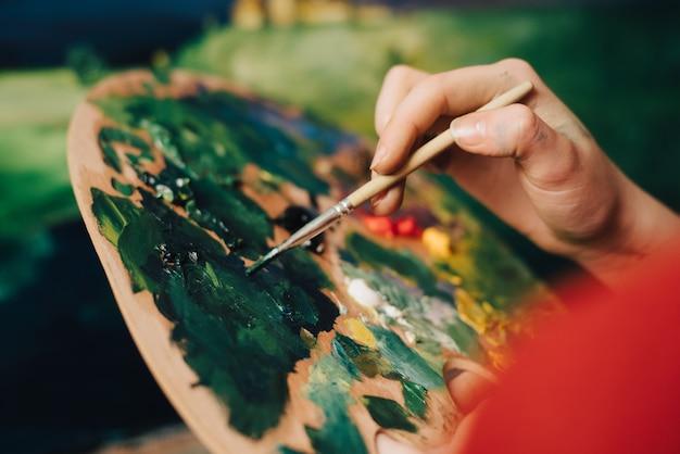 女性アーティストがイーゼルにブラシで絵を描く