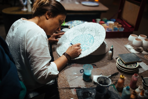 女性アーティストがセラミックプレートを描く