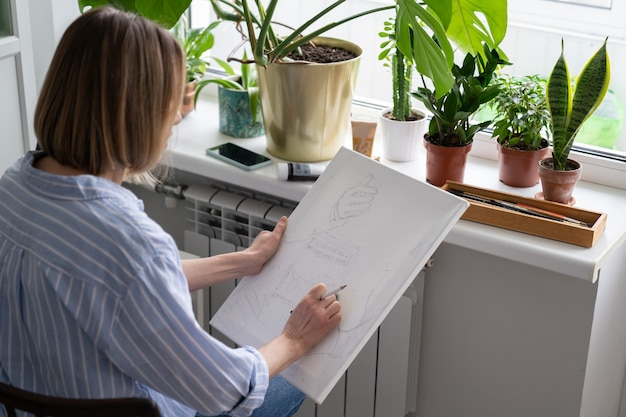 Woman artist paints a picture on canvas makes pencil sketches sitting at home during lockdown