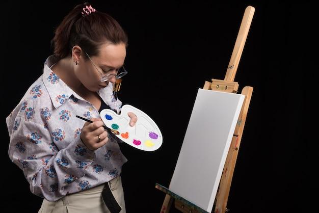 Artista donna dipinge un quadro su tela con la matita su sfondo nero