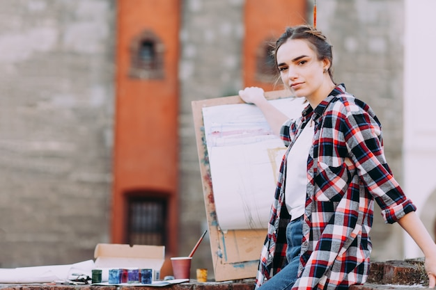 Woman artist paints a picture while sitting on a brick wall on a background of old architecture.