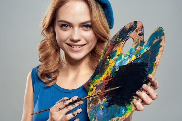 Палитра художника женщина с кистями в руках крупным планом художественного творчества.