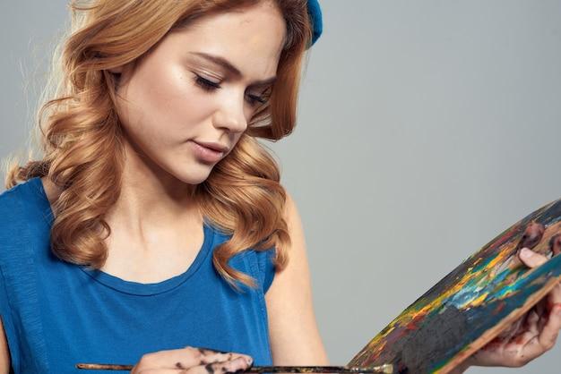 Палитра художника женщина с кистями в руках крупным планом художественного творчества