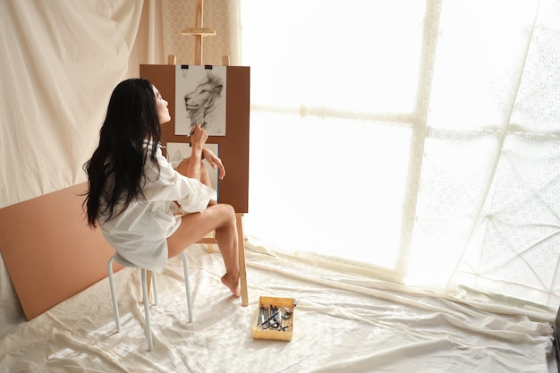 Woman artist in white shirt thinking something while drawing picture with pencil (woman lifestyle concept)