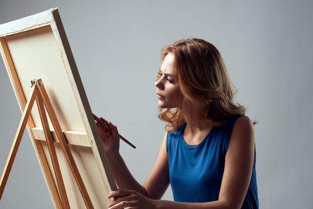 Художник женщины с краской кисти на стене света хобби искусства мольберта.