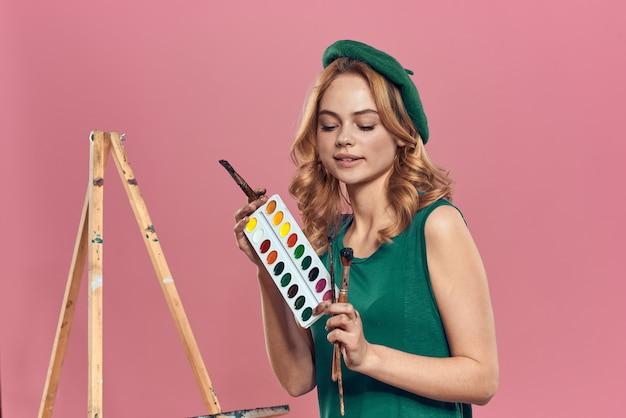 緑色のベレー帽と絵の具を持つ女性アーティスト