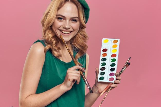 緑色のベレー帽を持つ女性アーティストが絵の具を保持します
