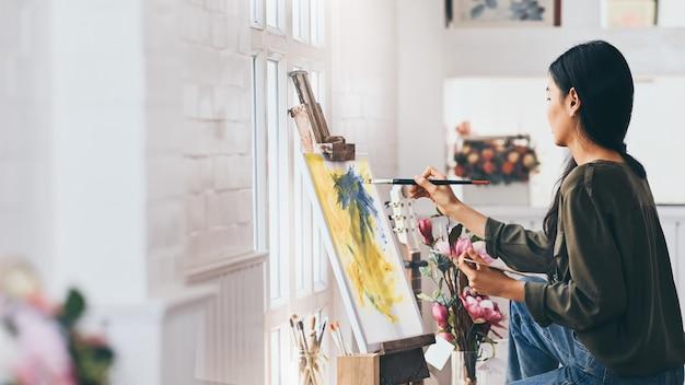 Женщина-художник работает над абстрактной акриловой живописью в художественной студии.