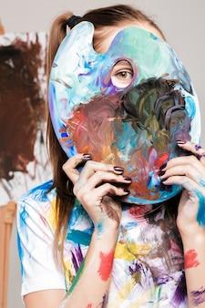 女性アーティストは、顔の前に絵の具でパレットを保持します