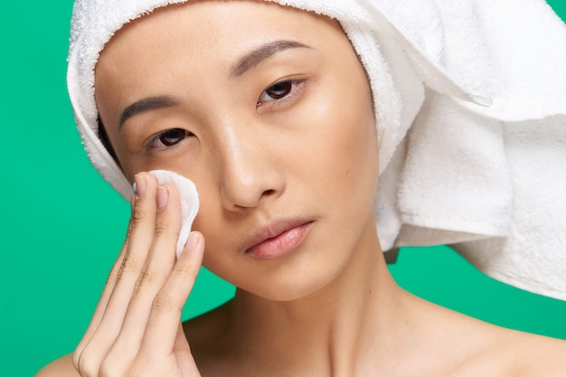 女性アジア人の外観きれいな肌のクローズアップスパトリートメントグリーン