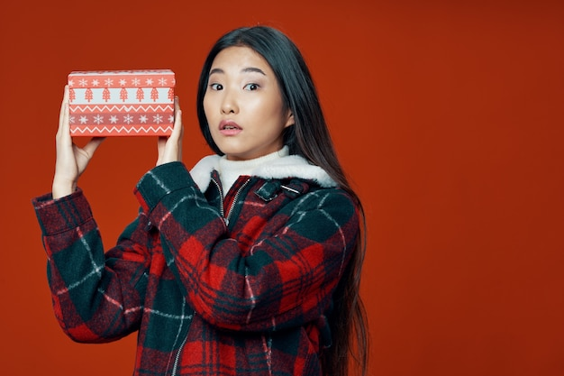 Woman of asian appearance in winter clothes gift for christmas isolated background