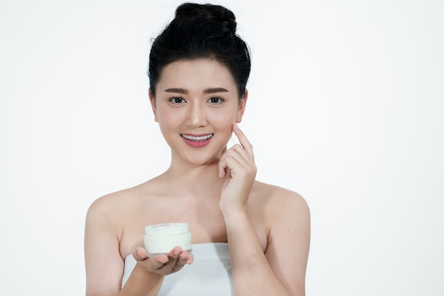 Woman asian using a skin care product a white background.girl is happy with the skin cream