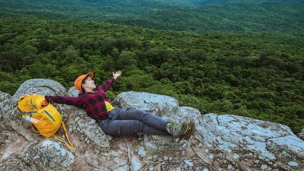 女性アジア人は休日にリラックスして旅行します。崖の上の山の自然を表示します。
