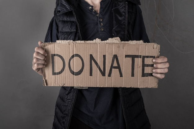女性は寄付のサインで助けを求めます。