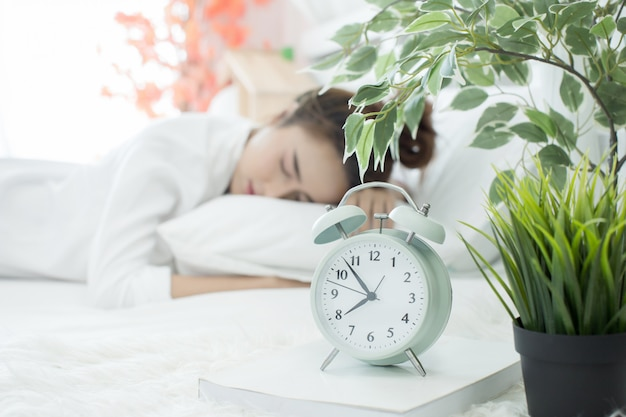 彼女のアラームが寝室で自宅で早い時間を示している間にベッドで眠っている女性