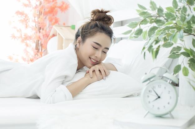 그녀의 알람 침실에서 집에서 이른 시간을 보여주는 동안 여자는 침대에서 자