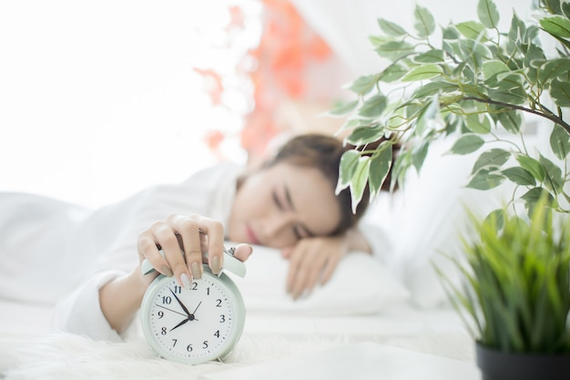Женщина спит в постели, а ее будильник показывает раннее время дома в спальне