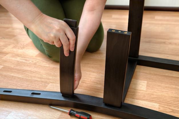 여자는 검은 나무 부품으로 식당 의자를 조립합니다.
