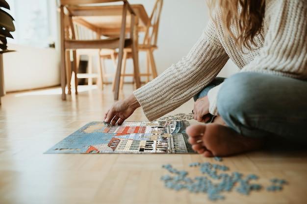 코로나바이러스 검역 기간 동안 코펜하겐 니하운의 직소 퍼즐을 조립하는 여성.