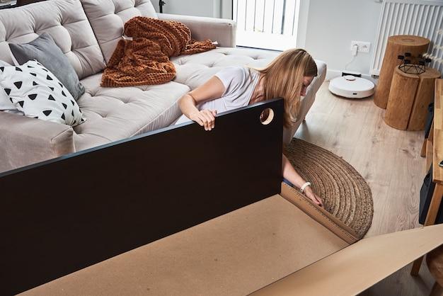 居間で家具を組み立てる女性