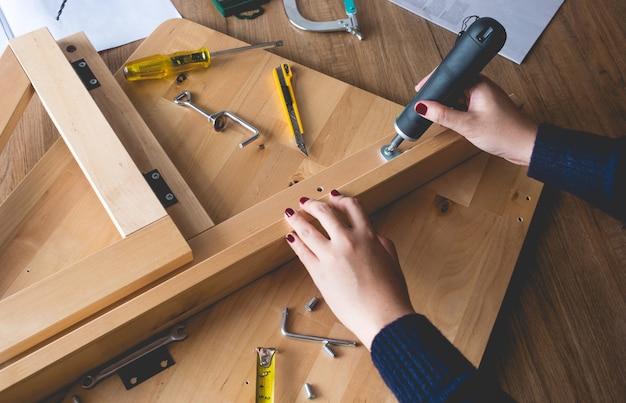 Женщина собирает деревянную мебель, ремонтирует или ремонтирует дом с помощью отвертки