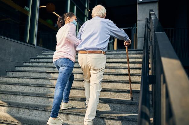 Woman assisting the senior man climbing staircase