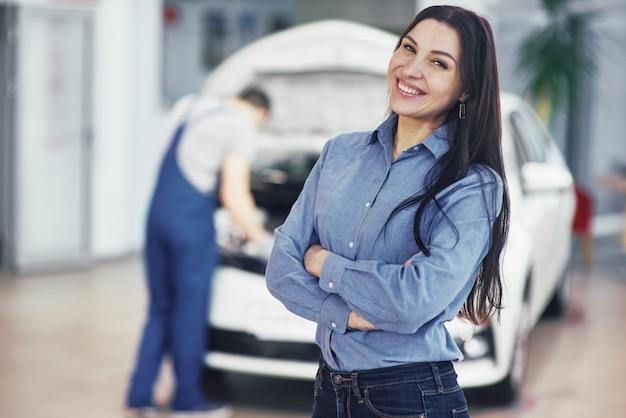 機械サービスを取得する車のガレージで女性。メカニックは車のボンネットの下で動作します