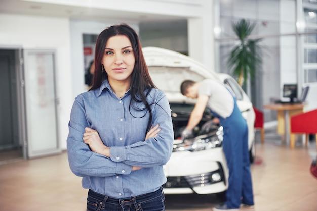 Женщина в гараже получает механическое обслуживание. механик работает под капотом автомобиля