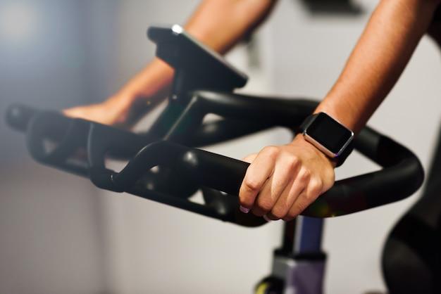 スマートな腕時計で紡績またはシクロ屋内で運動しているジムの女性