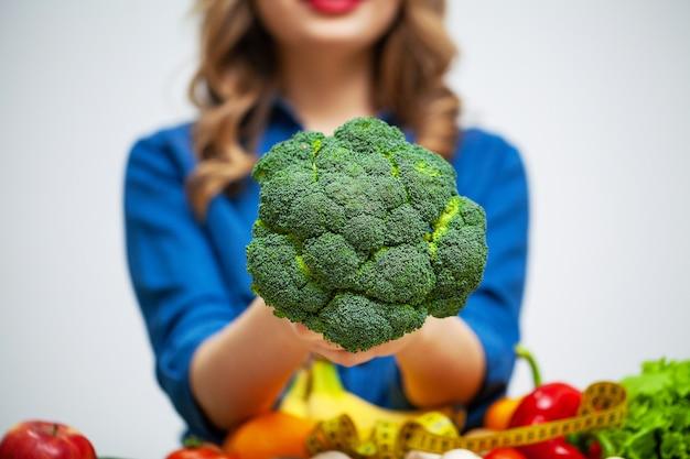 Женщина за столом держит брокколи на поверхности фруктов и овощей