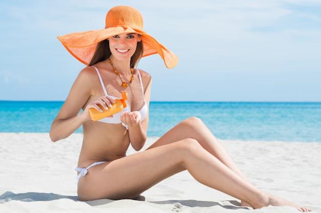 保湿剤とビーチで女性