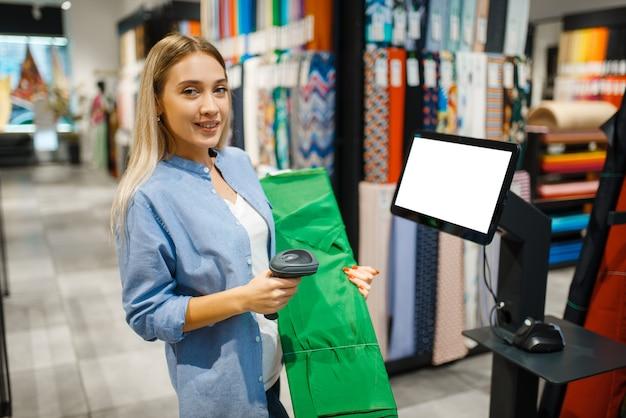 Женщина у кассы продает ткань в текстильном магазине. витрина с тканью для шитья