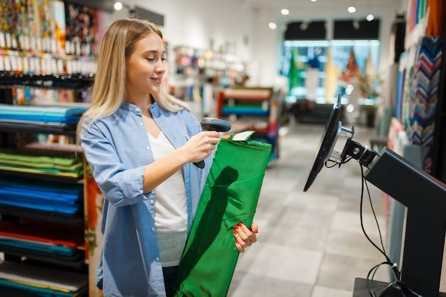 レジで女性は織物店で生地を販売しています。