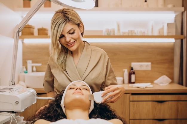 Женщина косметолога делает косметические процедуры