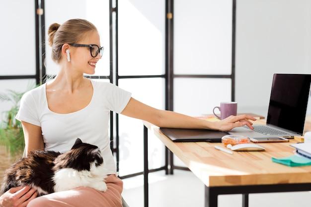 Женщина за столом работает на ноутбуке и держит кошку