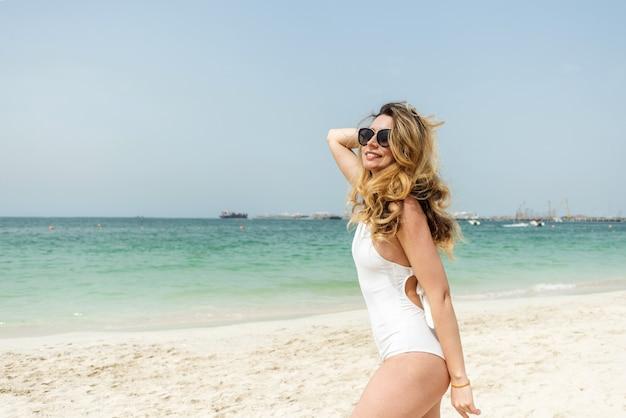 흰색 수영복을 입고 두바이 해변에서 여자