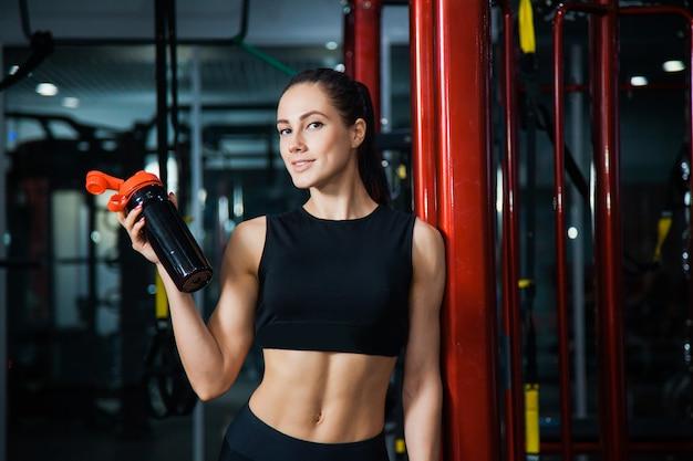Женщина в тренажерном зале держать шейкер с водой. спортсменка после тяжелой тренировки в спортивном клубе