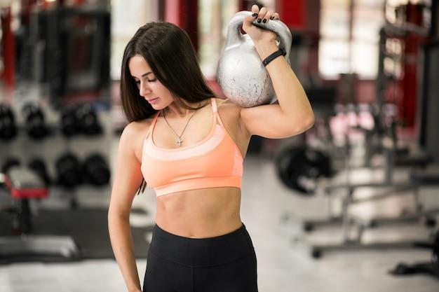Женщина в спортзале с гири