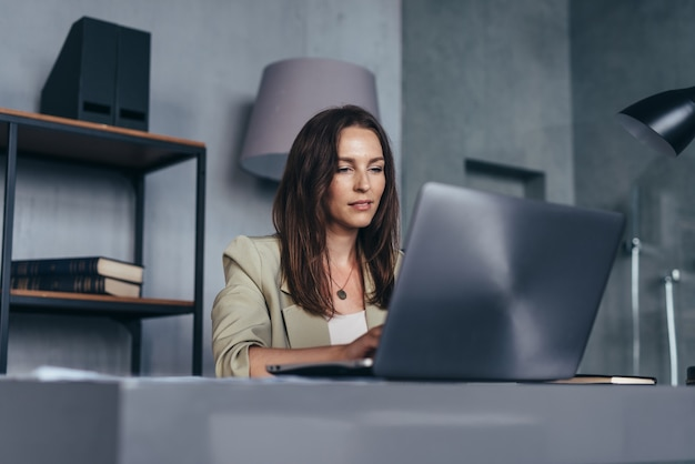 彼女のオフィスで働いているラップトップを持っている彼女の机の上の女性。