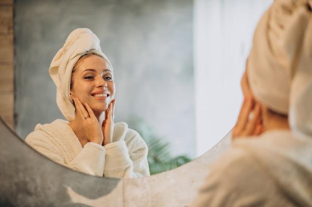 Женщина дома, применяя крем-маску