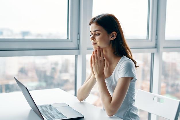 Женщина дома за столом перед рабочим офисом ноутбука