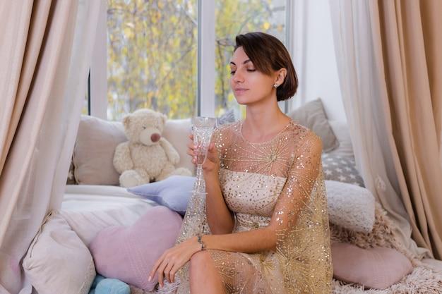 クリスマスの光沢のあるイブニングドレスを着て、シャンパンのガラスを保持している自宅の居心地の良い部屋の女性