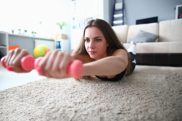 自宅でダンベルでフィットネスをしている女性。