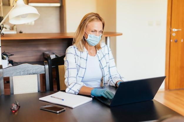 Женщина дома во время карантина работает на ноутбуке