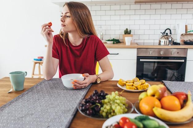 Женщина дома ест фрукты и овощи вид сверху.