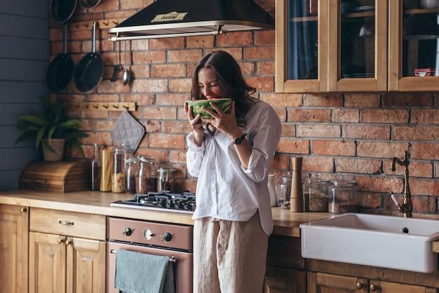 台所でスイカを食べている家の女性。